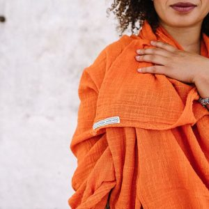 close up of orange khadi cotton wrap with logo