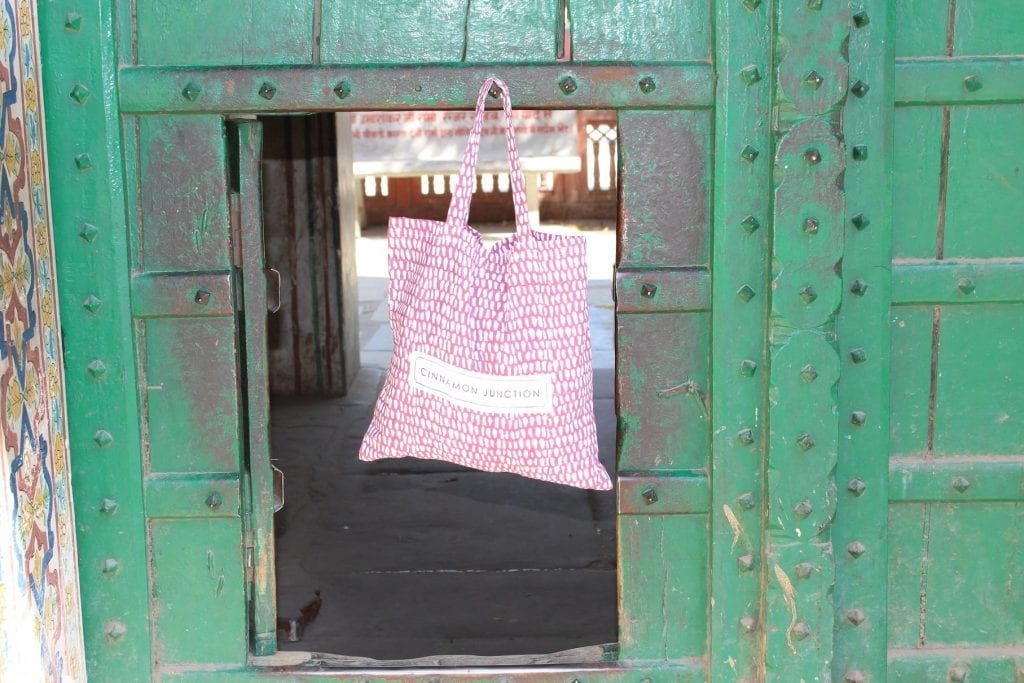 raspberry monsoon duvet set bag hanging from a green painted door