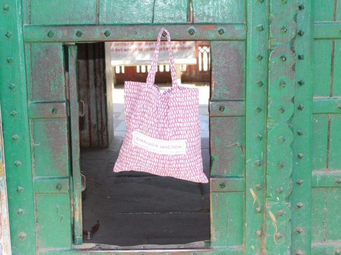 raspberry monsoon duvet set bag hanging from a green painted door
