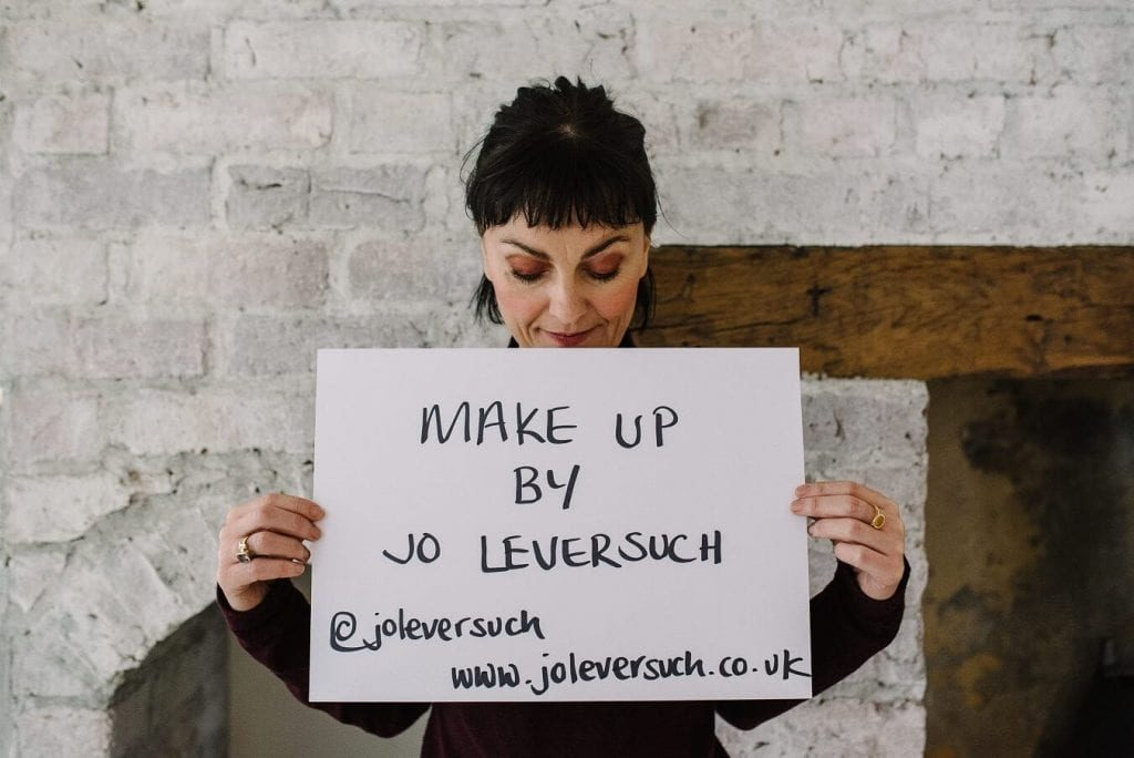 Jo Leversuch from Make Up by Jo, holding a card with social media details