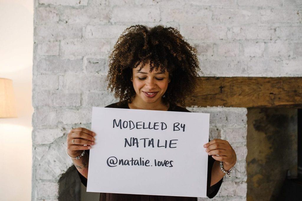 Natalie Lyons holding a card showing her Instagram details