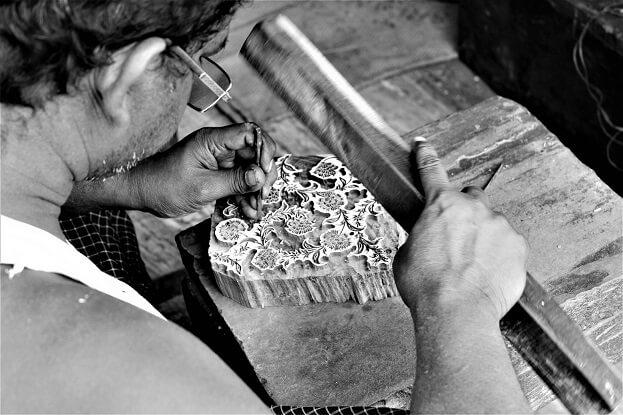 artisan craftsman carving a design into a wooden block