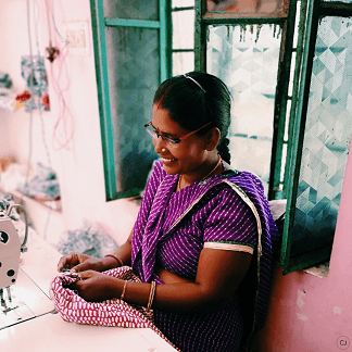 Manju sitting at a sewing machine in the workshop, sewing Monsoon bed linen