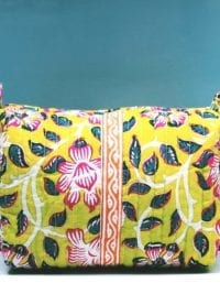 Block printed Citrus Dawn toiletry bag on a greeny blue background