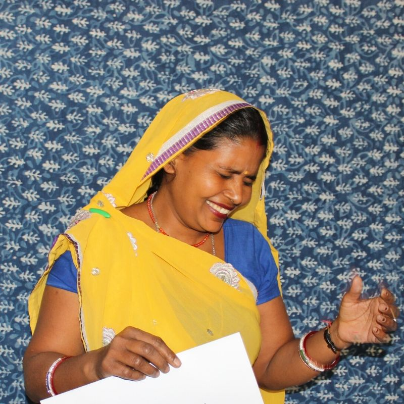 Manju laughing with her eyes shut wearing a yellow sari