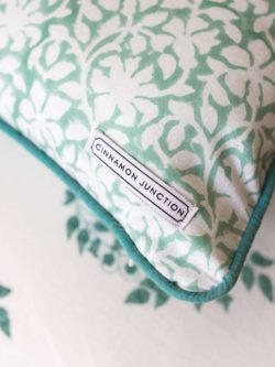 close up of Mint Heritage cushion on top of Mint Heritage duvet set
