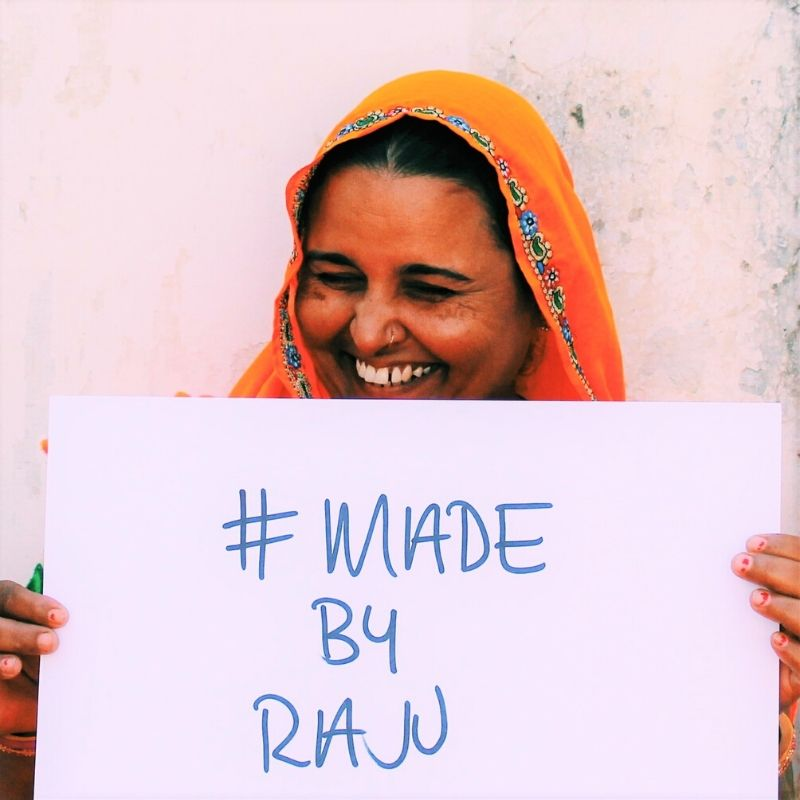 A laughing Raju in an orange sari, holding up a #made by raju card