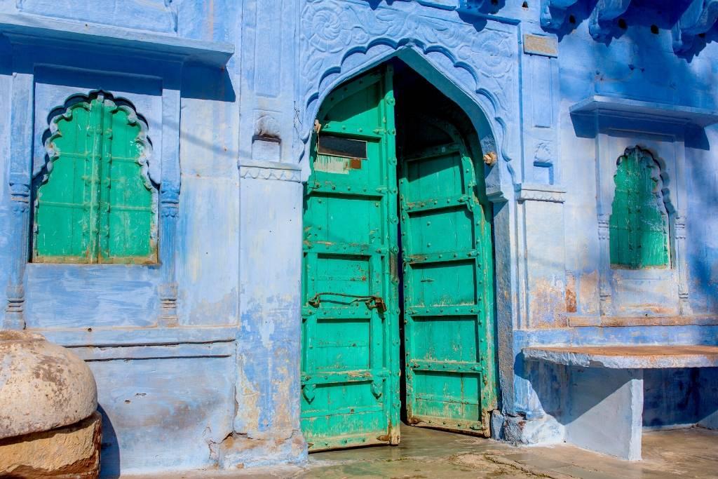 Green door in a Jodhpur building with indigo blue walls
