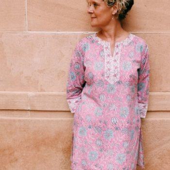 Kate wearing a ethical handmade block printed Maharani organic cotton tunic against a sandwashed wall