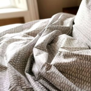 Close up of Dove Grey Indian Monsoon duvet cover and pillow on a bed
