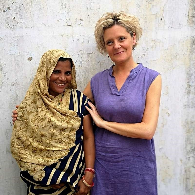Kate wearing the Kashmir Blue linen maxi dress and standing with Basanti at the workshop in Jaipur