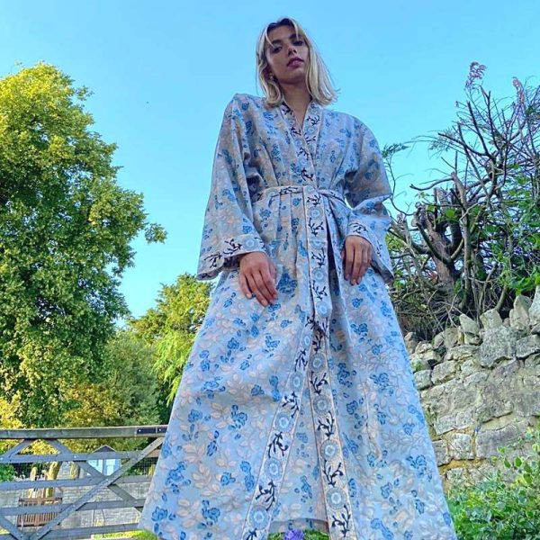Ollie wearing blue and peach kimono looking down at camera